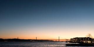 Landschap op zonsondergang van de rivier Tagus en de 25ste april-brug Stock Foto