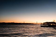 Landschap op zonsondergang van de rivier Tagus en de 25ste april-brug Royalty-vrije Stock Foto