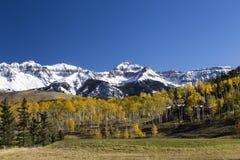 Landschap van Colorado met groot die huis onder kleurrijke bomen wordt genesteld en sneeuw bereikte bergen een hoogtepunt royalty-vrije stock afbeeldingen