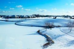 Landschap van Curvy op de sneeuw behandelde golfcursus en vijver. Stock Foto's
