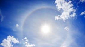 Landschap van de blauwe hemel met zon, witte wolken en halo Royalty-vrije Stock Foto
