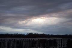 Landschap van de hemel met donkere wolken wordt behandeld waardoor de zon die breekt royalty-vrije stock afbeelding