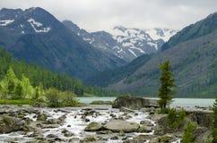 landschap van de rivier die op stenen onder bergen en het hout lopen Royalty-vrije Stock Afbeeldingen