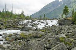 landschap van de rivier die op stenen onder bergen en het hout lopen Stock Afbeelding