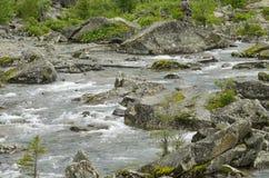 landschap van de rivier die op stenen onder bergen en het hout lopen Royalty-vrije Stock Fotografie