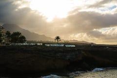 Landschap van de rotsachtige kust van de Atlantische Oceaan met enige palm en bewolkte hemel Zacht geel ochtendlicht Royalty-vrije Stock Foto's