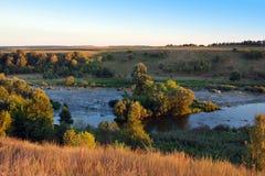 Landschap van de vallei, rivier, bomen, gebied, en een hemel Stock Afbeelding