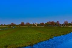 Landschap van een landbouwbedrijf met een windmolen stock afbeelding