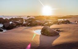 Landschap van een strand met rotsen tijdens zonsondergang royalty-vrije stock fotografie