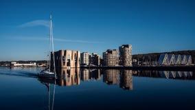 Landschap van gebouwen dichtbij de pijler Jacht op de achtergrond van nieuwe gebouwen Blauwe kleur stock fotografie