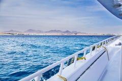 Landschap van het dek van een jacht op zee en bergen op de horizon, tegen een blauwe hemel met wolken, Royalty-vrije Stock Fotografie