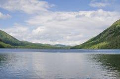 Landschap van het meer onder bergen en het hout Stock Afbeeldingen
