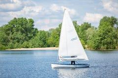 Landschap van meer met wit jacht op heldere zonnige de zomerdag Blauwe hemel met witte wolken over grote meren en groene bomen en stock afbeeldingen
