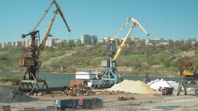Landschap van sleepboten en kranen in scheepswerf in ladingshaven De kraan beweegt zand door vrachtwagens in een ladingsterminal