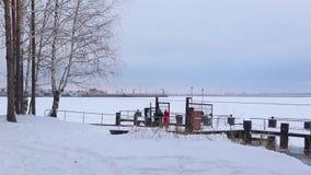 Landschap van snow-covered bank en rivierpijler waarop de tribunes in liefde koppelen stock videobeelden