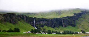 Landschap van spectaculaire klippen met watervallen en landbouwbedrijven in zuidelijk IJsland in een bewolkte dag stock foto