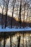 Landschap van wilde rivier met de bezinning van de zonsonderganghemel in de bergen, in de winter Stock Foto
