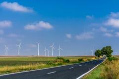 Landschap van windturbines en asfaltweg het uitrekken zich in t Royalty-vrije Stock Foto