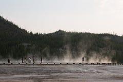 Landschap van Yellowstone-promenade met gesilhouetteerde toeristen die in stoom lopen royalty-vrije stock foto's