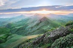 Landschap zonsondergang bij de bovenkant van de groene bergen die het overzees overzien Stock Afbeelding