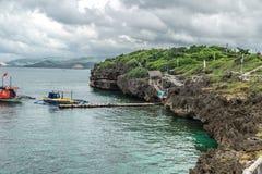 Landschaps azuurblauwe overzees en een rotsachtig klein eiland van kustcrystal cove dichtbij Boracay-eiland in de Filippijnen stock foto