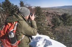Landschapsfotografie: een mensenwandelaar met een rugzak schiet een landschap in een de winterbos royalty-vrije stock afbeelding