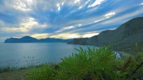 Landschapszonsondergang op een achtergrond van bergen en overzees Stock Foto's