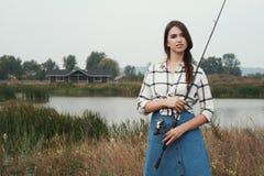 landsdamanseende mot dammet på ranch med fisk-stången royaltyfri fotografi