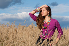 Landsflicka som fixar hennes hår i fält mot blå bakgrund för molnig himmel Royaltyfria Bilder