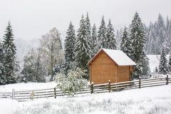 Landshus under tungt snöfall i Carpathians berg Fotografering för Bildbyråer