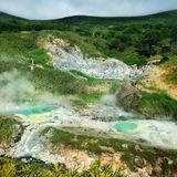 Landskap av ön av Iturup med vårar av sulphuric vatten Kurils Ryssland Arkivfoto