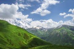 Landskap av berg och gräs- kullar på solig sommardag i Svaneti, Georgia Moln för blå himmel och vitöver det georgian berget royaltyfri foto