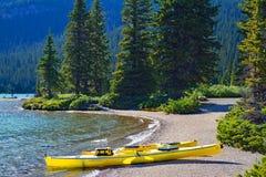 Landskap av blåa Hector Lake med kanoter i den Banff nationalparken, Kanada fotografering för bildbyråer