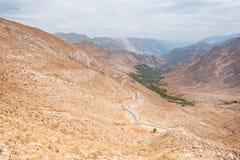 Landskap av de fantastiska färgrika röda bergen över den tunna krökta asfaltvägen i stenig kanjon Arkivbild
