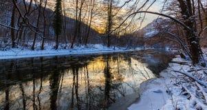 Landskap av den lösa floden med solnedgånghimmelreflexion i bergen, i vinter Royaltyfri Bild