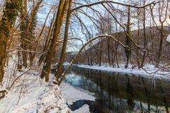 Landskap av den lösa floden med solnedgånghimmelreflexion i bergen, i vinter Royaltyfri Foto