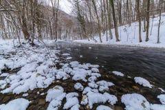 Landskap av den lösa floden med solnedgånghimmelreflexion i bergen, i vinter Arkivbild