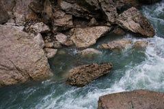 Landskap av den snabba bergfloden som flödar mellan grova stenar Royaltyfri Bild