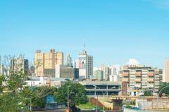 Landskap av den stora staden av Campo Stad med några byggnader mellan träd, biltrafik och stads- konst Royaltyfri Fotografi
