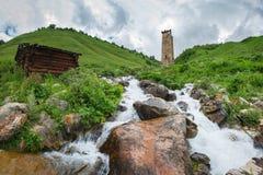 Landskap av en bergström i byn av Adishi, Svaneti, Georgia med Svan ett forntida torn på en kulle Royaltyfri Foto
