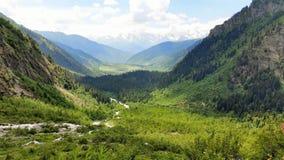 Landskap av en härlig grön dal med berg för glaciär` s i bakgrunden och molnig himmel i övreSvaneti, Georgia Arkivfoto