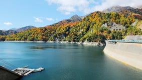 Landskap av höstsjön med fartyg som parkerar vid lakesiden och berg av färgrik lövverk vid den Kurobe fördämningen Royaltyfri Fotografi