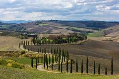 Landskap av kullar, landsvägen, cypressträd och lantliga hus, Tuscany Fotografering för Bildbyråer