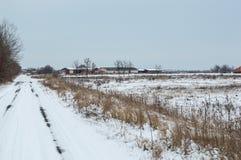 Landskap av lantgårdbyggnader i vinterdagen Arkivfoton