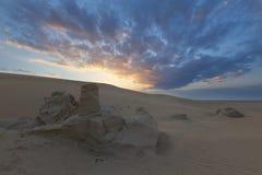 Landskap av sanddyn och vaggar med moln på solnedgången arkivbilder