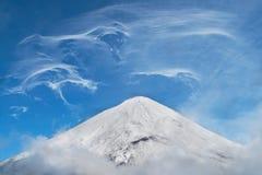 Landskap av snöig berg, konstiga spridda moln och dimma fotografering för bildbyråer