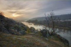 Landskap av solnedgången över den sydliga felfloden Morgonsolen gör dess väg till och med de fluffiga molnen och dimman royaltyfria foton