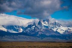 Landskap av steniga berg och fluffiga moln Shevelev Royaltyfri Fotografi