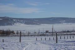Landskap av vägen som täckas i snö till byar med bakgrund för bergskedja och för blå himmel royaltyfri fotografi