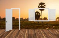 Landskap bak det öppningsdörren och fönstret Arkivbilder